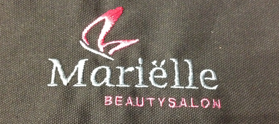Multi kleur geborduurde borst logo's op kappers cape.